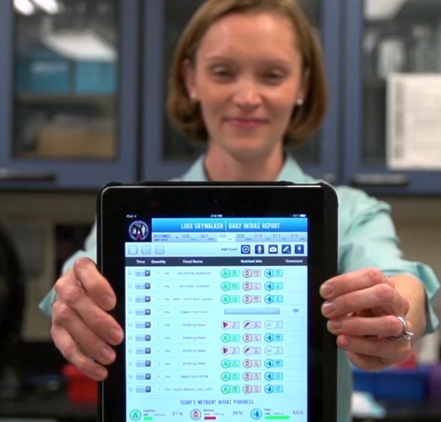 NASA scientist, Sara Zwart, holding an iPad running ISS FIT app.
